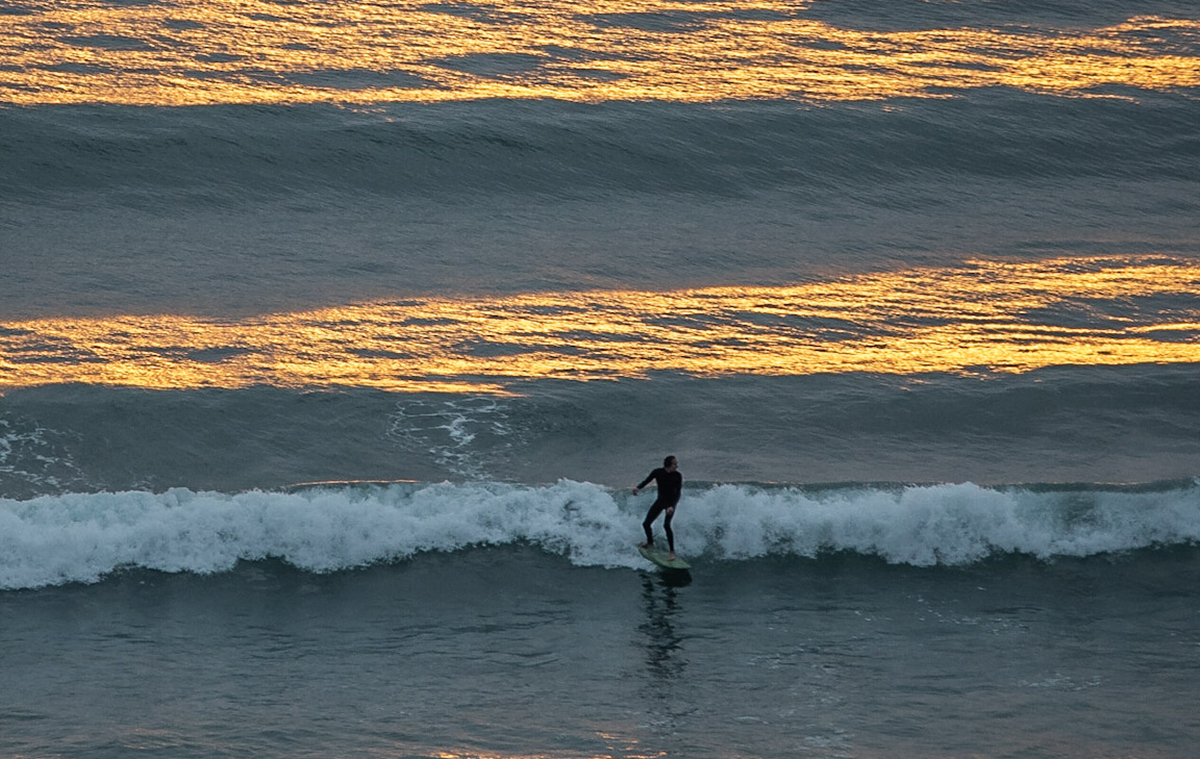 Surfing in a stunning sunset at Saunton sands beach North Devon